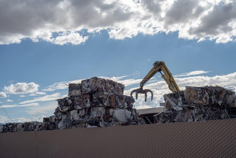 Kraan die kubussen van samengeperst metaal stapelen bij het recycling van centrum royalty-vrije stock foto