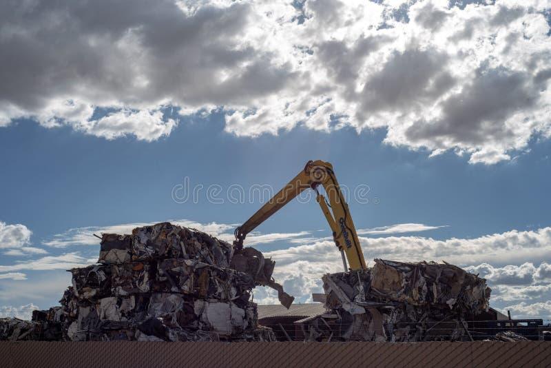 Kraan die kubussen van samengeperst metaal stapelen bij het recycling van centrum stock foto