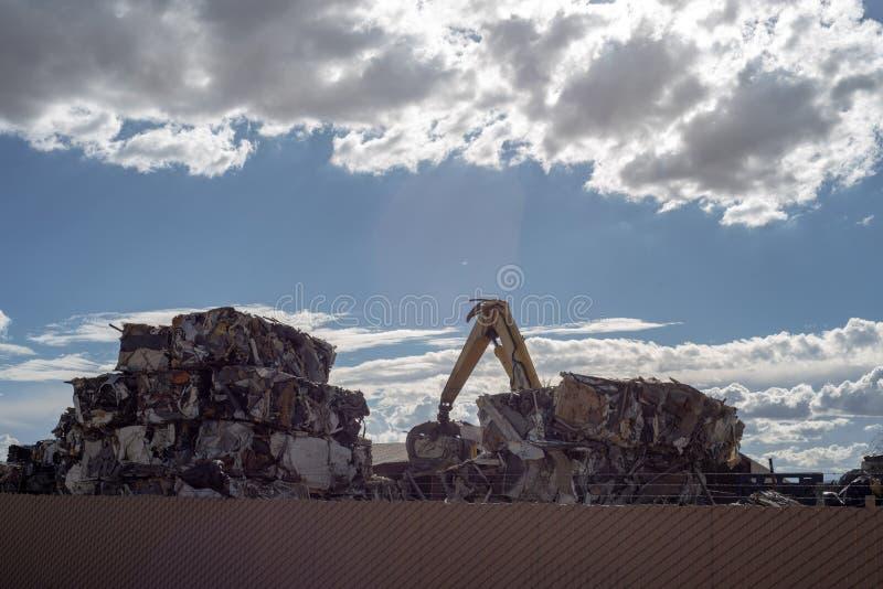 Kraan die kubussen van samengeperst metaal stapelen bij het recycling van centrum stock afbeelding