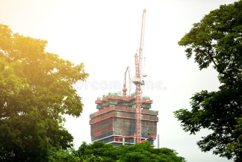 Kraan en bouwconstructieplaats tegen tussen groene boom stock afbeelding
