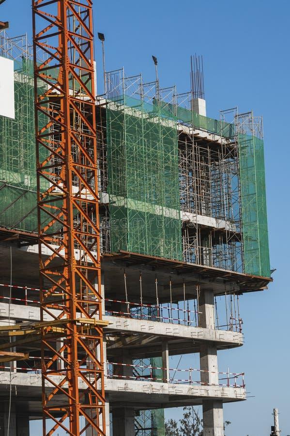 Kraan en bouwterrein tegen blauwe lucht Metaalconstructie van onafgewerkt gebouw bij de bouw Tower royalty-vrije stock fotografie