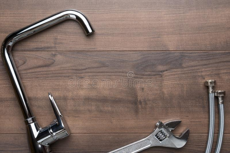 Kraan, moersleutel, flexibele slangschakelaars over houten achtergrond met exemplaarruimte royalty-vrije stock foto's