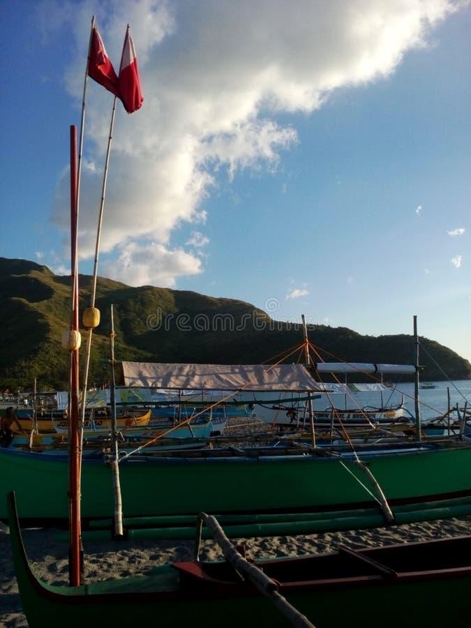 Kraanbalkboten, hulpmiddelen en vlaggen op Pundaquit-Strand in schemeringen dichtbij San Antonio, Filippijnen stock foto
