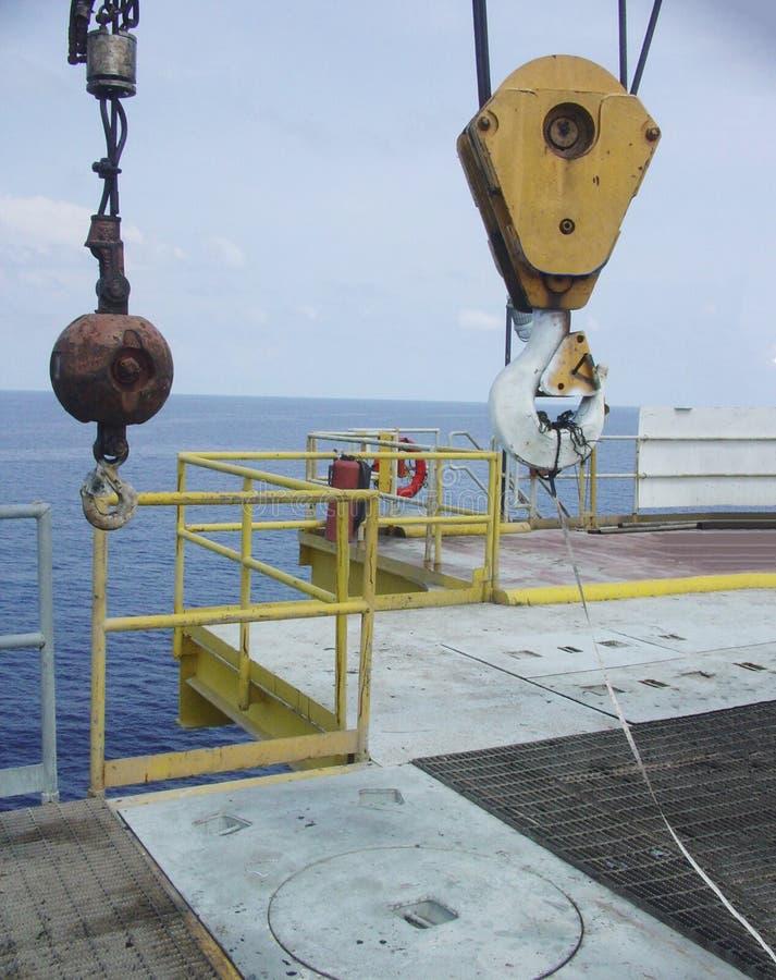 Kraanhijstoestel, hoofd en hulphaken met veiligheidsklinken en het leiden slinger op het verre zeeplatform van de aardolieproduct stock afbeeldingen