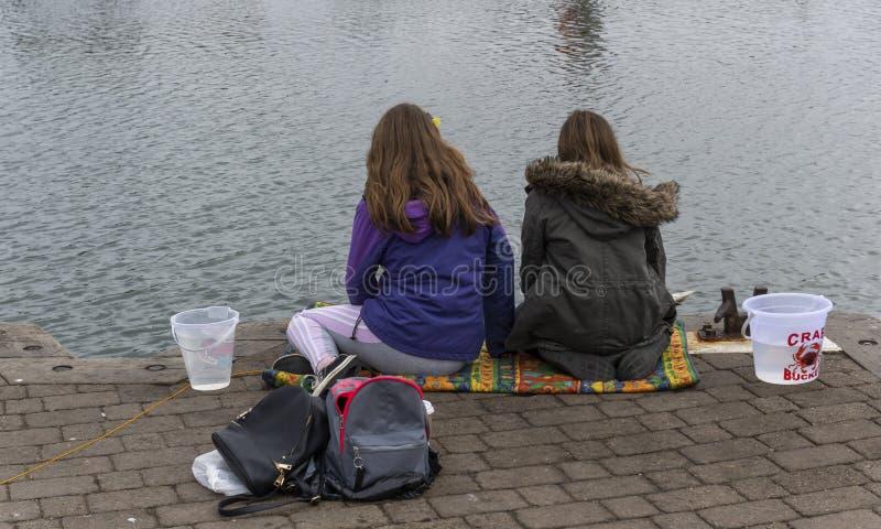 Krab die Twee Meisjes in Haven vissen stock foto's