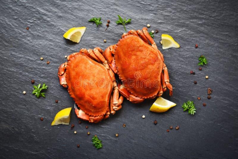 Krabben met citroen op plaat worden gekookt op donkere plaat hoogste mening wordt gediend - de steenkrab stoomde zeevruchten die royalty-vrije stock foto's