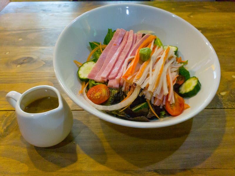 Krabben-Stöcke und Ham Vegetable Salad mit japanischer Soße des indischen Sesams auf dem Holztisch stockfoto