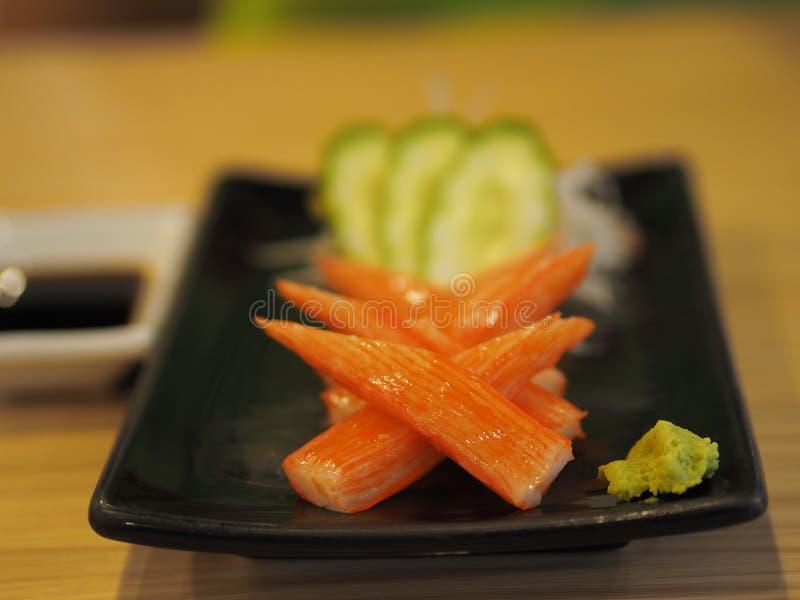 Krabbenstöcke in einem schwarzen Teller gesetzt auf eine Tabelle Japanische Nahrungsmittel stockbilder