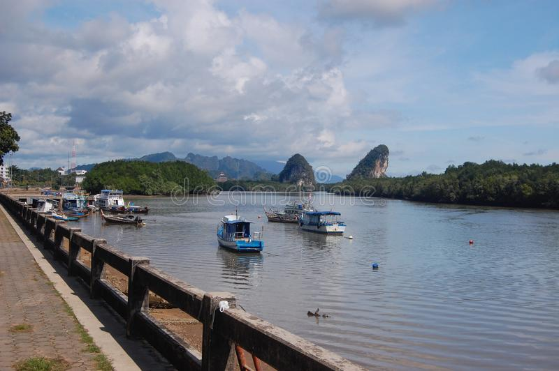 Krabi City View towards the Karst Mountains in Krabi, Southern Thailand in the beautiful blue sky with a river and boats in the ba. Ckground royalty free stock images