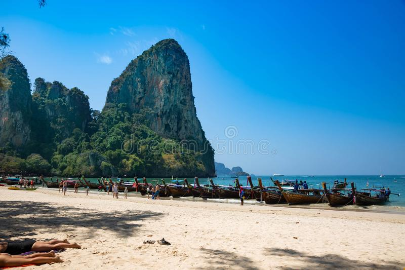 Krabi province, Railay beach, Thailand - February 18, 2019: Long-tailed taxi boats stand in a row on Ao Nang beach. Tourists on royalty free stock photos