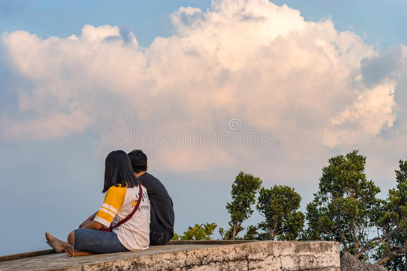 A young couple of local Thai teenagers in nature sitting on a stone against the sky stock image