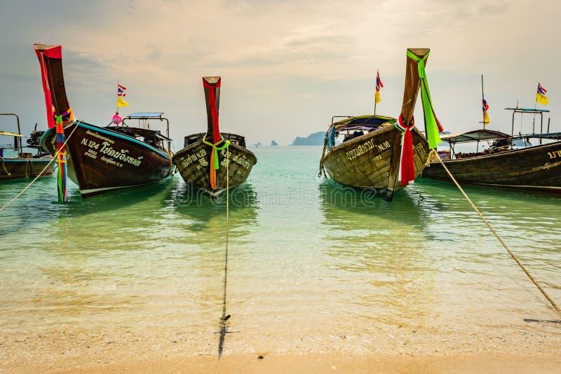 KRABI, TAILANDIA - NOVIEMBRE DE 2018: Barcos de madera tradicionales tailandeses con la decoración de la cinta en la orilla del o foto de archivo libre de regalías