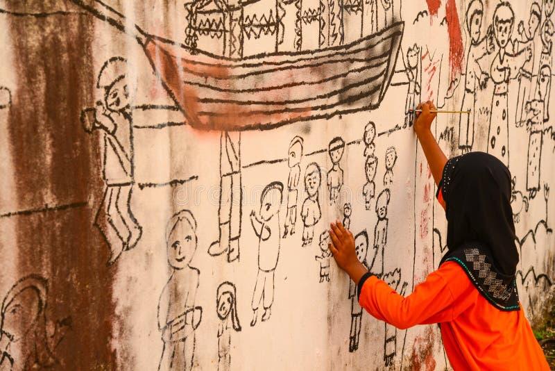 Muslim girl drawing graphic image on wall. Krabi, Thailand - May 3, 2015: Muslim girl wearing black hijab drawing graphic image on wall of ruined house in Krabi royalty free stock photo