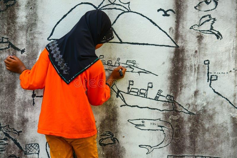 Muslim girl drawing graphic image on wall. Krabi, Thailand - May 3, 2015: Muslim girl wearing black hijab drawing graphic image on wall of ruined house in Krabi stock photo