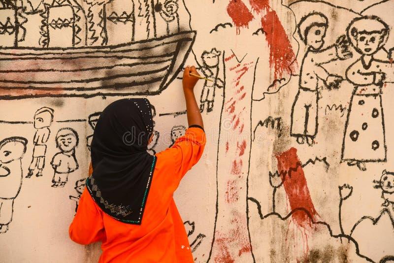 Muslim girl drawing graphic image on wall. Krabi, Thailand - May 3, 2015: Muslim girl wearing black hijab drawing graphic image on wall of ruined house in Krabi royalty free stock image