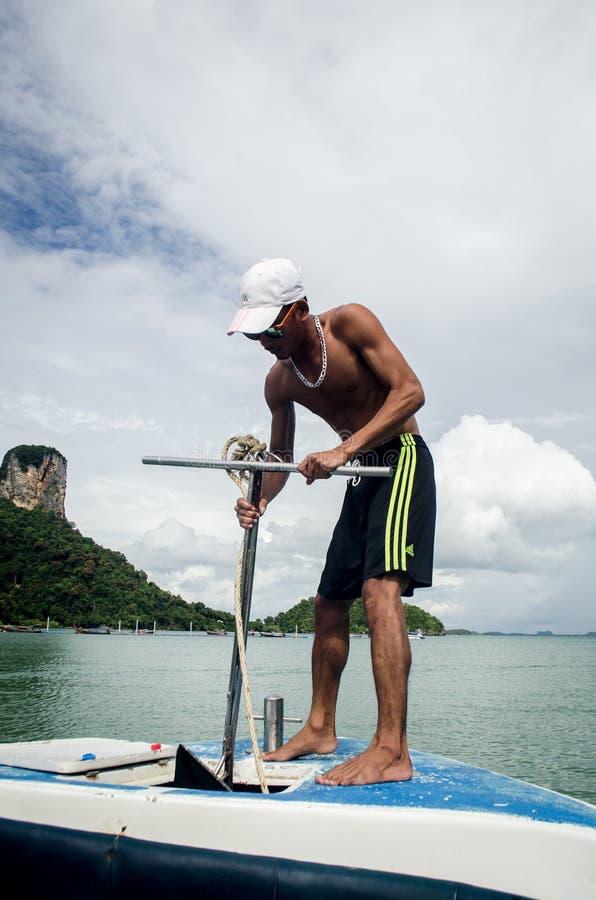 KRABI, THAILAND, 6 NOV.: lokale boatman die een achor in tou laten vallen royalty-vrije stock foto