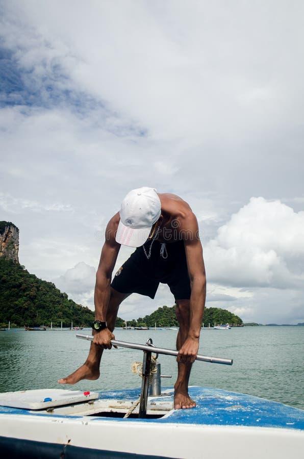 KRABI, THAILAND, 6 NOV.: lokale boatman die een achor in tou laten vallen stock afbeelding