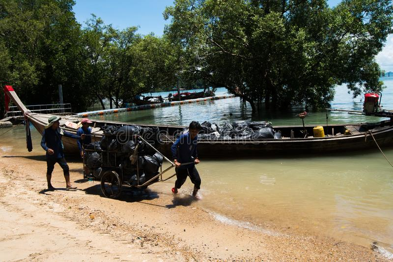 Urban sanitary vehicle garbage loader Ship. Krabi, Thailand - September 29, 2018 ; Volunteer Worker collects trash Garbage and carry to loader boat ship, to move royalty free stock photo