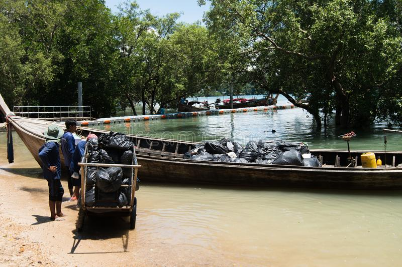 Urban sanitary vehicle garbage loader Ship. Krabi, Thailand - September 29, 2018 ; Volunteer Worker collects trash Garbage and carry to loader boat ship, to move stock image