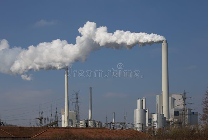 Krachtcentrale met schoorstenen en witte rook stock afbeeldingen