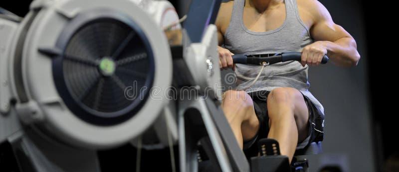 Krachtige aantrekkelijke spiermens CrossFit trainer do workout op binnenroeier bij de gymnastiek royalty-vrije stock foto