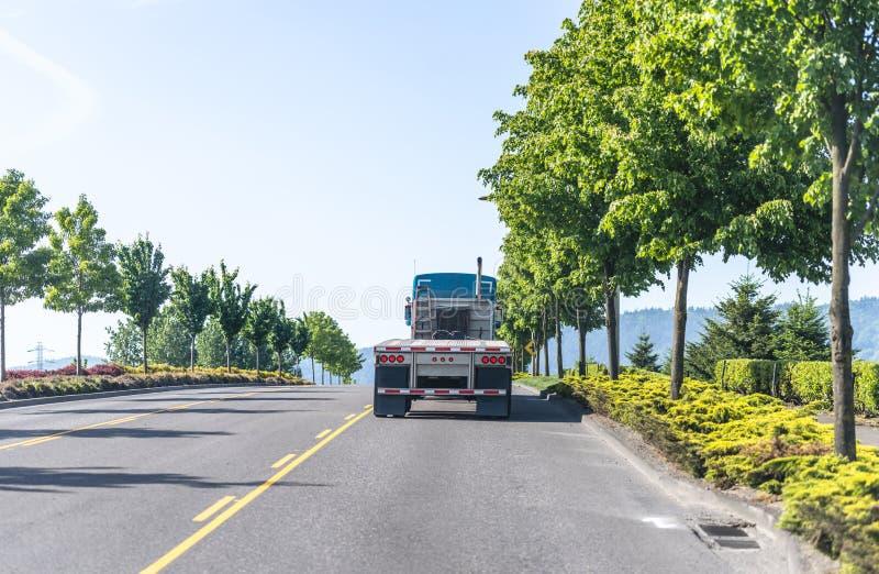 Krachtige blauwe grote installatie semi vrachtwagen met lege vlakke bed semi aanhangwagen die op de weg naar pakhuis voor ladings royalty-vrije stock foto's