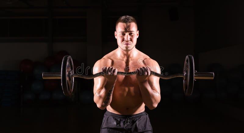 Krachtige bodybuilder die de oefeningen met barbell doen Sterk mannetje met naakt torso op donkere achtergrond Sterkte en royalty-vrije stock afbeeldingen