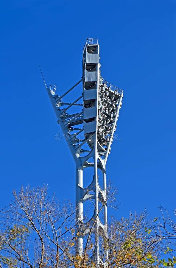 Krachtige de bouwpyloon van de verlichtingsschijnwerper dichtbij stadion op blauwe hemel in zonnige dag, stock afbeeldingen