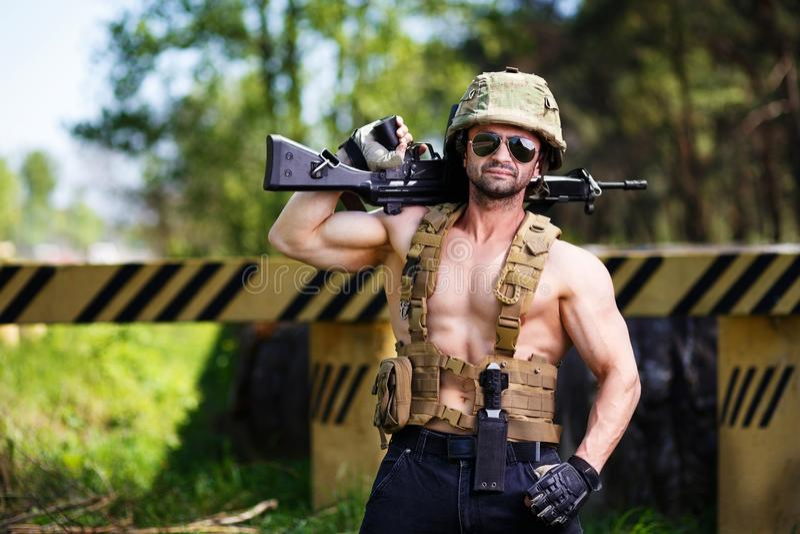 Krachtige huurling die met machinepistool een wegversperring bewaken stock fotografie
