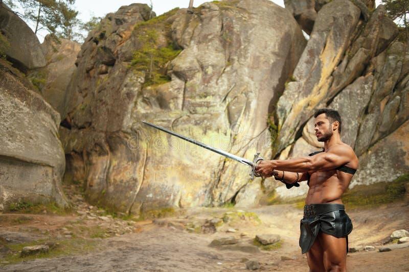 Krachtige jonge strijder met een zwaard stock fotografie