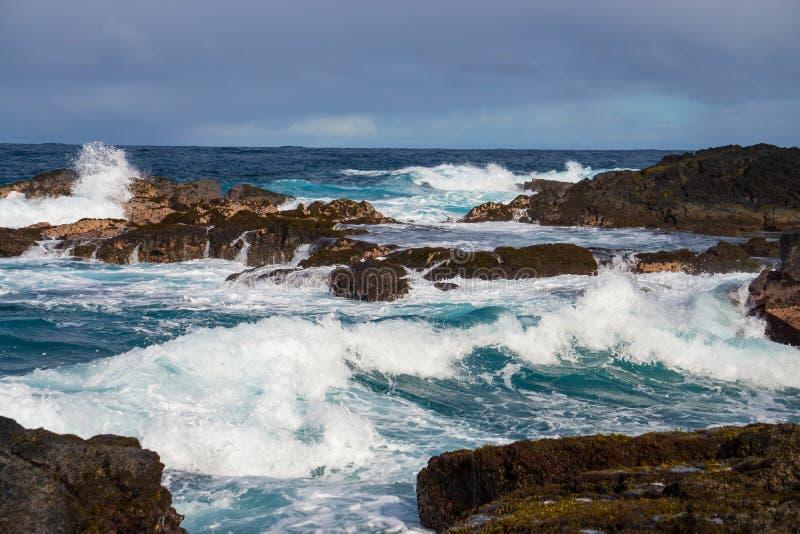 Krachtige Kustonderbreking op Lava Rock Coast van Hawaï met het Bespatten stock foto
