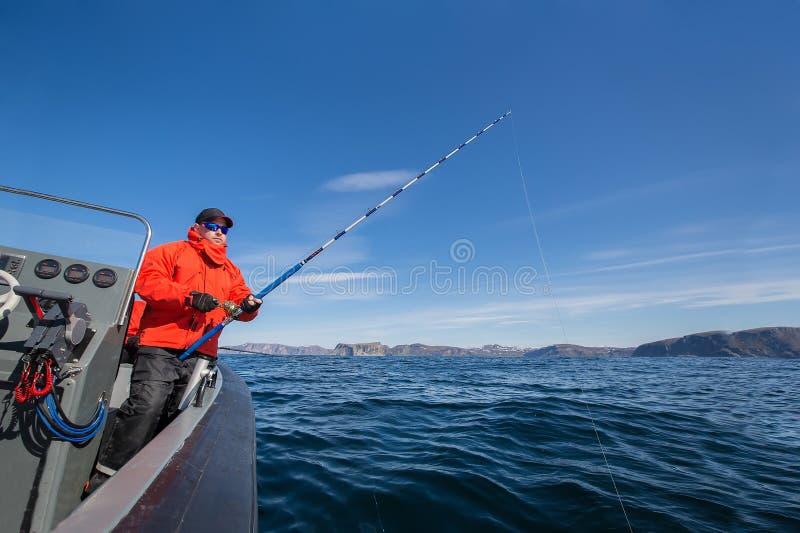 Krachtige mens met een hengel in zijn handen overzeese boot fisherma stock afbeeldingen