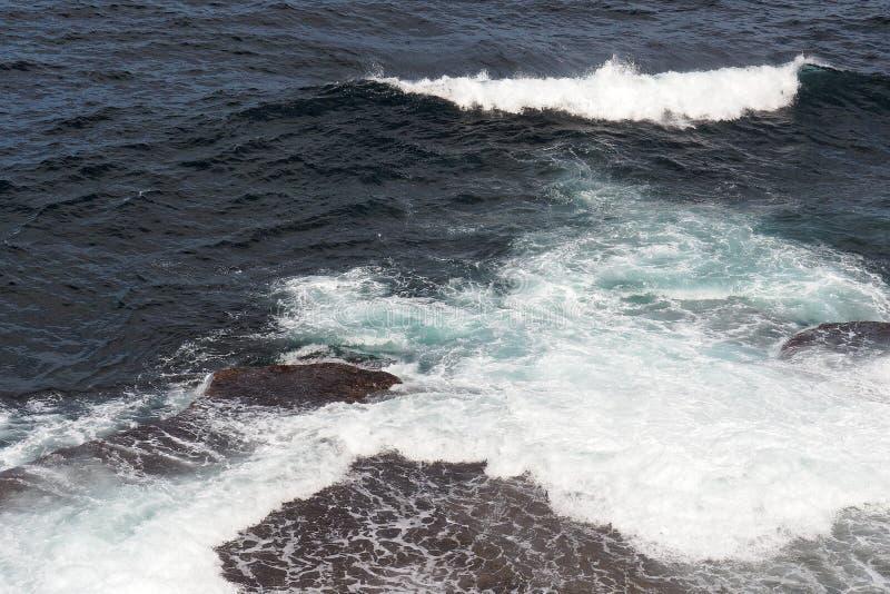 Krachtige Vreedzame Oceaangolven die op Rotsen verpletteren stock afbeeldingen