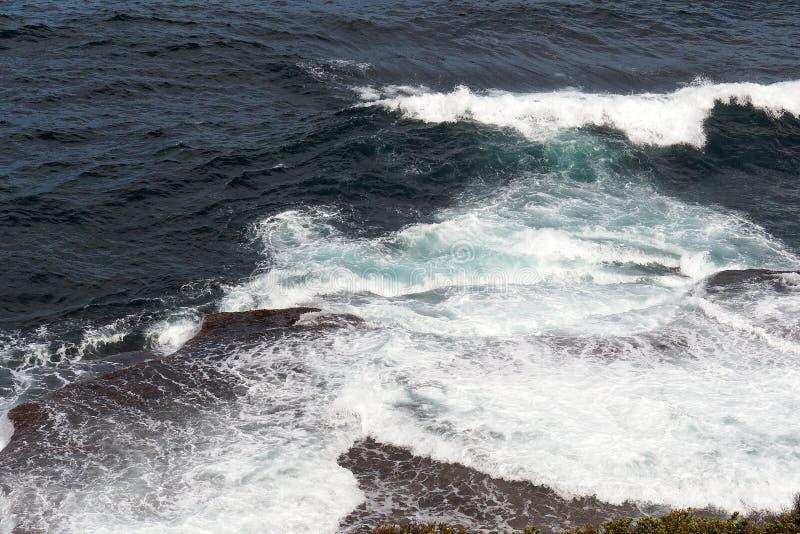 Krachtige Vreedzame Oceaangolven die op Rotsen verpletteren stock fotografie
