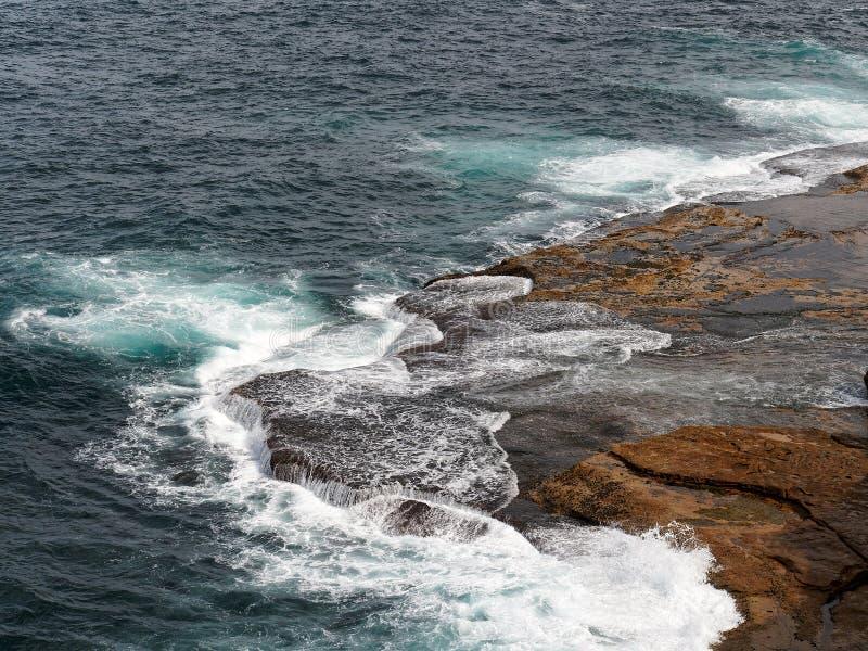 Krachtige Vreedzame Oceaangolven die op Rotsen verpletteren stock afbeelding