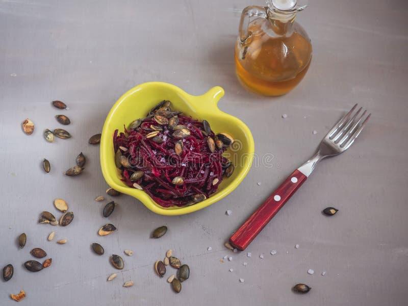 Kraciaści gotowani buraki z słonecznikowymi i dyniowymi ziarnami w żółtym ceramicznym sałatkowym pucharze w tle, butelka jarzynow obrazy stock