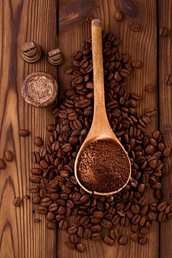 Kraciasta kawa w łyżce na piec kawowych fasoli tle zdjęcie stock