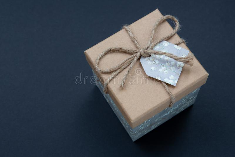 Kraft gift box on a dark contrasted background, decorated with a textured bow and feathers, creating a romantic atmosphere. Typica. Lly used for birthday royalty free stock image