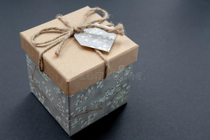 Kraft gift box on a dark contrasted background, decorated with a textured bow and feathers, creating a romantic atmosphere. Typica. Lly used for birthday royalty free stock photos