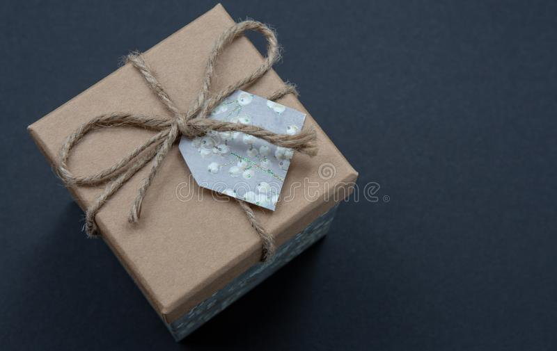 Kraft gift box on a dark contrasted background, decorated with a textured bow and feathers, creating a romantic atmosphere. Typica. Lly used for birthday royalty free stock images