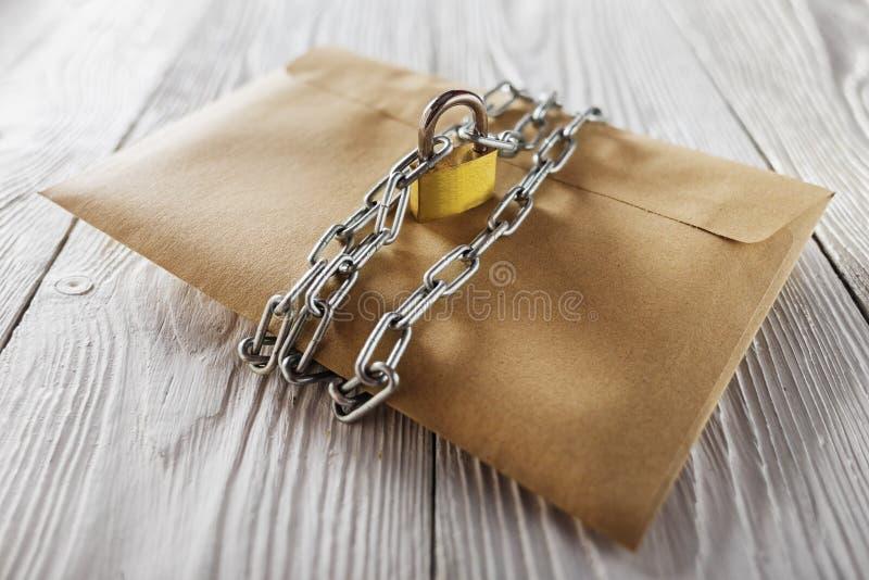Kraft kuvert med bokstäver och hänglås, kedja på gammal vit träbakgrund Skydd av din stolpe, posta för PC Mellanrum för th arkivbild