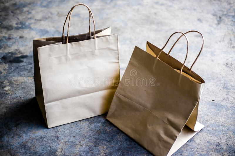 Kraft paper shopping bags. On cement background royalty free stock photo
