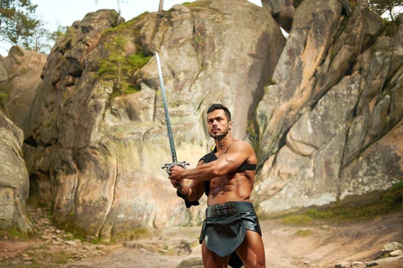 Kraftfull ung krigare med ett svärd arkivbilder