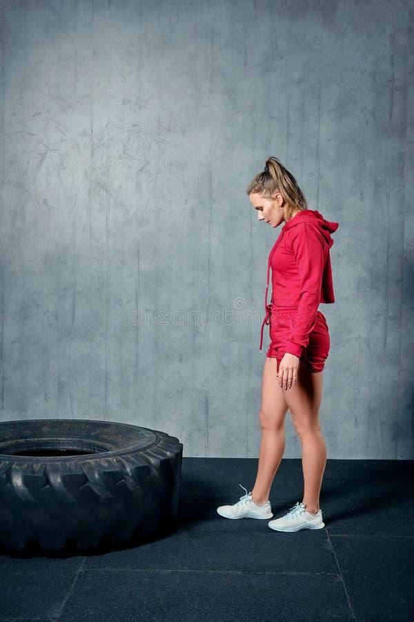 Kraftig attraktiv muskulös flicka som kopplas in i idrottshallen, utbildning med jätte- gummihjul i idrottshallen arkivfoton