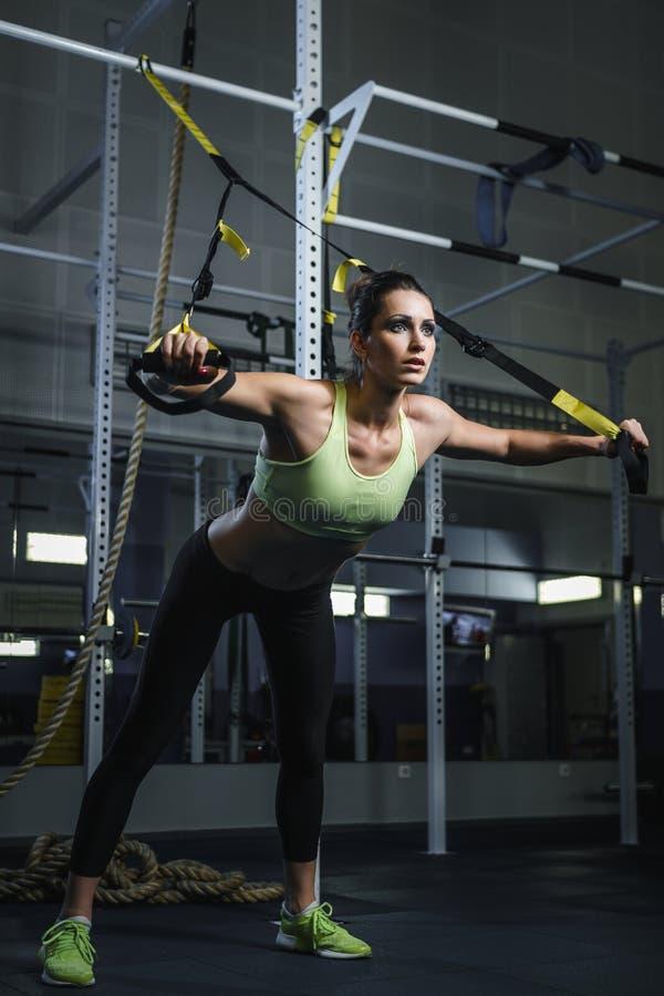 Kraftig attraktiv muskulös kvinnaCrossFit instruktör som utarbetar på idrottshallen royaltyfri bild