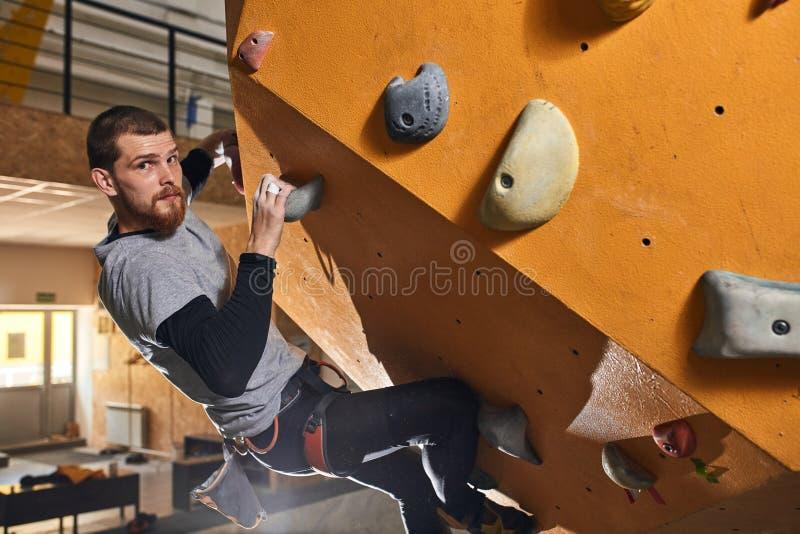 Kraftig fysiskt utmanad man som hårt utbildar på att klättra grupper arkivfoton
