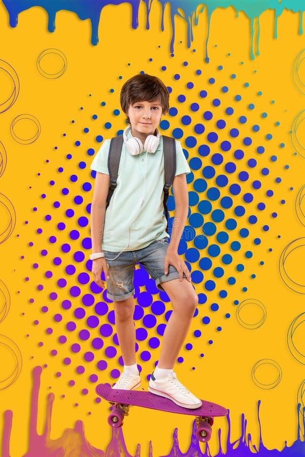 Kraftig glad pojke som förbereder sig för ritt på skateboarden royaltyfri bild