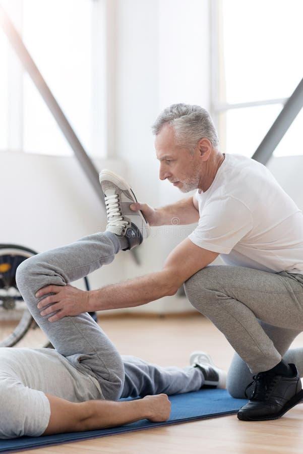 Kraftig ortoped som sträcker det handikappat i idrottshallen royaltyfria foton