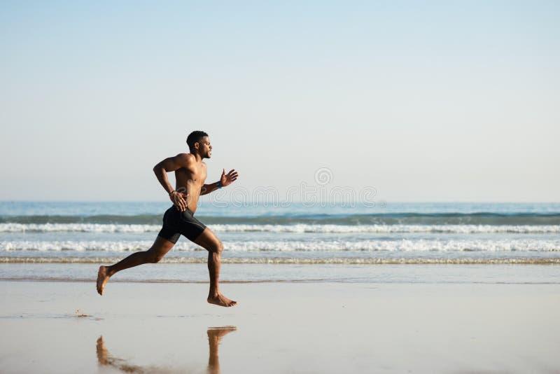 Kraftig svart man som barfota kör förbi havet fotografering för bildbyråer