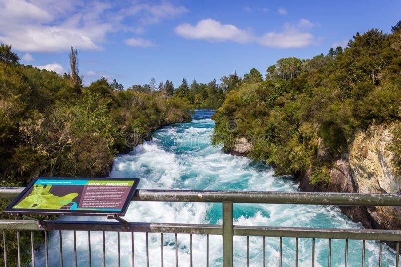Kraftiga Huka nedgångar med ett tecken med information om nedgångarna, på den Waikato floden nära Taupo den norr ön Nya Zeeland royaltyfri foto